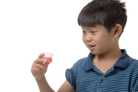 hesitant: Cute boy holding up some pink liquid medicine with uncertain look on his face