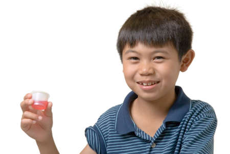 Cute boy holding up some pink liquid medicine with uncertain look on his face