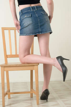 long skirt: Sexy legs leaning on chair Stock Photo