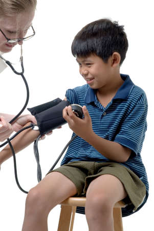 doctor's appointment: Young asian boy examined by caucasian woman doctor