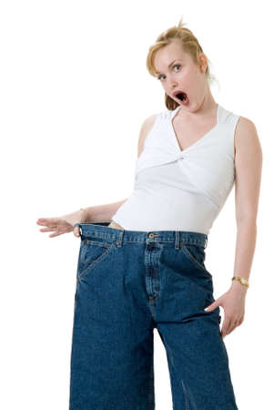 obtain: Woman demonstrating weight loss by wearing an old pair of jeans four sizes too big and pointing to her stomach Stock Photo