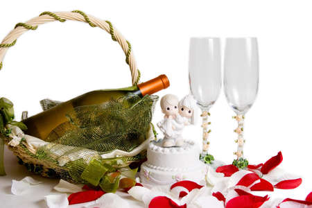basket with bottle of wine and wine glasses on rose petals photo