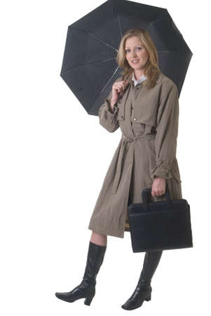 Confident business woman dressed in trenchcoat with umbrella