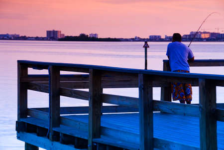 Man fishing off a pier in Florida at sunset Stock Photo - 524281