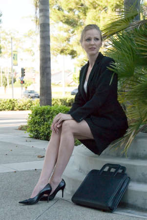 Blonde business woman sitting outside photo