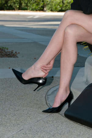 legs of businesswoman in high heels sitting and rubbing ankle photo