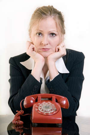 Woman sitting in front of old retro rotary style red telephone leaning on hands waiting for the good job to call
