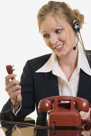 business woman looking at the plug end of an old fashioned red rotary phone Stock Photo - 599222