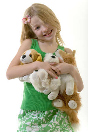 cute little eight year old girl with flower in her hair holding a handful of stuffed animals Stock Photo - 675630