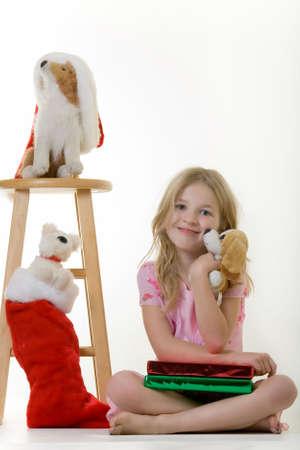 old year: cute piccolo una ragazza di otto anni che siede sul pavimento con la tenuta dei presenti di natale un cane farcito poco Archivio Fotografico