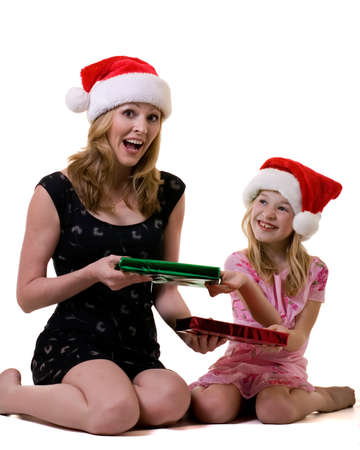 attractive mother and eight year old daughter wearing santa hats exchanging christmas gifts photo