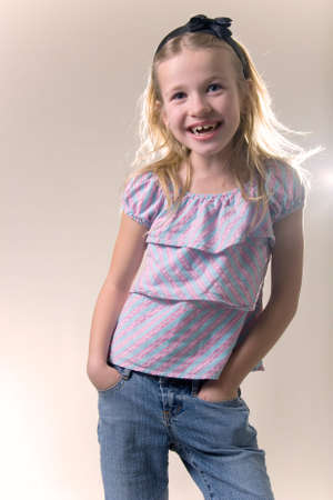 8 year old: cute blonde little eight year old girl in purple shirt smiling with hands in pockets of jeans