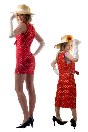 cute little eight year old girl wearing white gloves and too big high heeled shoes and large red polka dot dress standing beside a grown up woman in same clothes Stock Photo