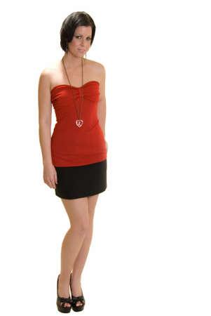 red tube: Corpo pieno di una bella bruna sexy rosso in alto a tubo corto e nero mini gonna in piedi su sfondo bianco