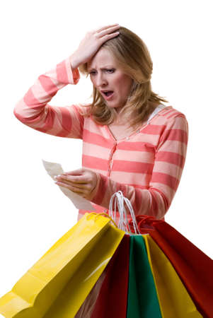 Attractive blond woman standing in front of a bunch of colorful shopping bags checking over the receit with a worried expression Stock Photo