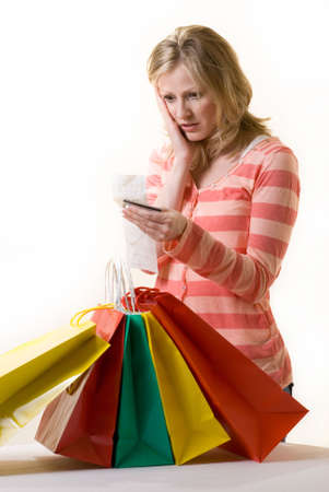 overspending: Attractive blond woman standing in front of a bunch of colorful shopping bags checking over the receit with a worried expression Stock Photo