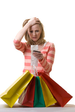 Attractive blond woman standing in front of a bunch of colorful shopping bags checking over the receit with a worried expression photo