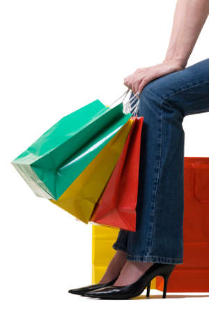 Legs of a woman holding onto a bunch of colorful shopping bags photo