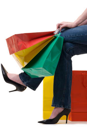 Legs of a woman holding onto a bunch of colorful shopping bags