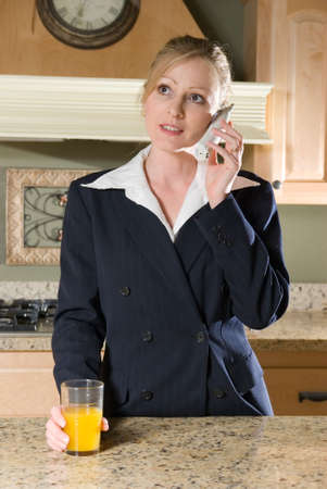 Stock photo of a woman wearing a business suit standing in kitchen with a glass of orange juice talking on the phone