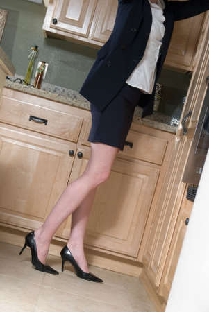 Stock photo of an attractive womans legs reaching up to kitchen cupboards as if making dinner still wearing office clothes photo