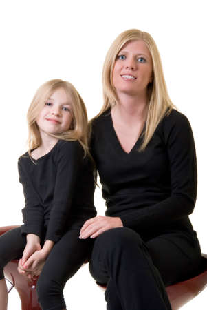 attire: faces of attractive mother and eight year old daughter sitting together on white
