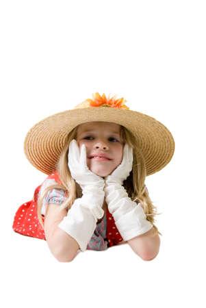 old year: Piccolo otto anni ragazza indossa guanti bianchi e troppo grande cappello di paglia di alta posa su di riposo stomaco mento sulla pianura mani su sfondo bianco  Archivio Fotografico