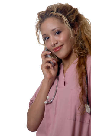 Attractive smiling blond nurse talking on cell phone wearing pink scrubs standing on white background Stock Photo - 827712