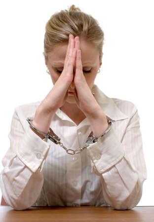 handcuffed: Blonde professioneel uitziende vrouw draagt een wit shirt met collared handen geboeid met ellebogen op tafel leunend op handen voor het concept van witte collared criminaliteit