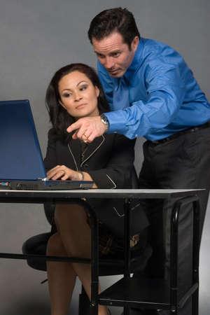 delegar: Hombre de negocios que est� parado detr�s de un compa�ero de trabajo de la mujer que se sienta en su escritorio que se�ala en la pantalla de computadora