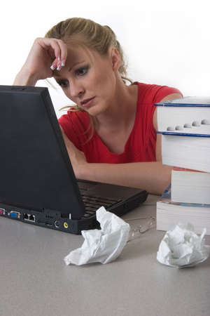 final thoughts: Young woman sitting in front of laptop beside a pile of thick textbooks and crumpled paper with hand on forhead looking stressed