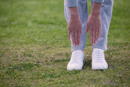 flexable: Feet of a woman outside standing on the grass bending down with hands reaching to touch feet