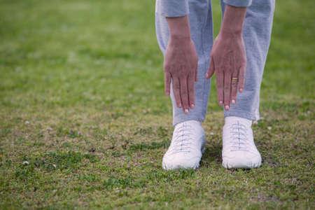 bending down: Pies de una mujer fuera de pie sobre la hierba agacharse con las manos para llegar a tocar los pies