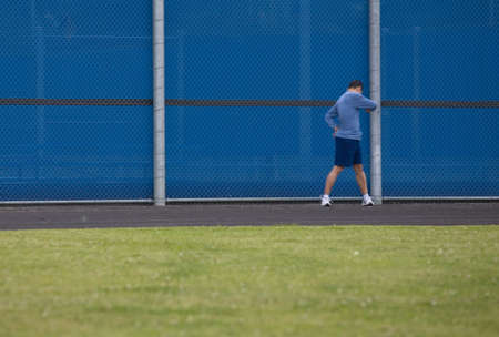 Man outside standing on the grass twisting at the waist for a warm up before starting to run on an outdoor track