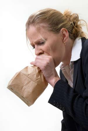 Blonde vrouw die een bruine papieren zak over de mond met een radeloze meningsuiting als een paniekaanval of nauseated Stockfoto