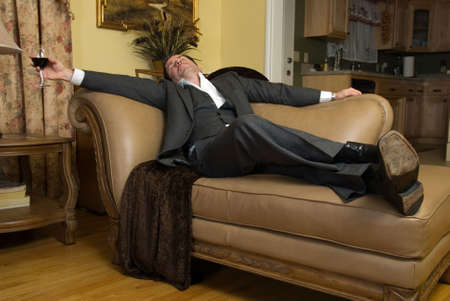 sofa: Man in a business suit sleeping on the sofa with a glass of red wine still in his hand Stock Photo