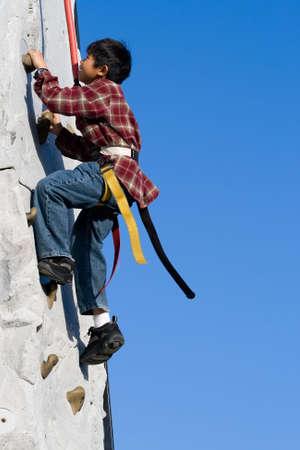 S'élever extérieur de jeune garçon asiatique sur un mur s'élevant de roche avec le ciel bleu clair dans le fond Banque d'images - 905869