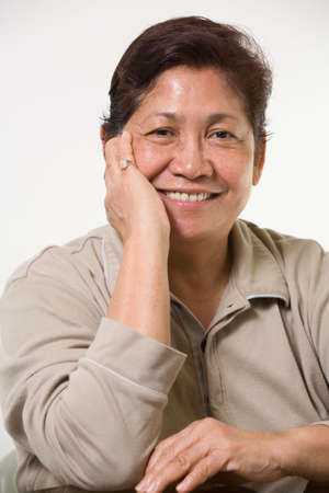 Portrait of a senior asian woman smiling with hand on face Stock Photo