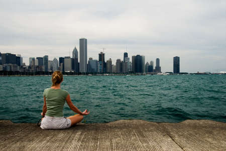 Young woman doing meditation exercise by Lake michigan with city view of downtown chicago