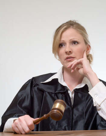 court judge: blond woman judge holding a gavel with serious expression as if listening to someone speaking
