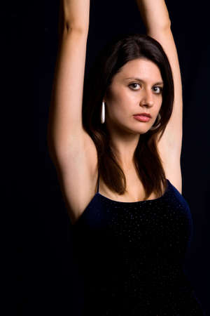 Beautiful Armenian woman wearing sexy black dress with arms reaching up with serious expression over black background Stock Photo - 925092