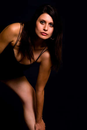 Beautiful armenian woman wearing sexy black dress bending down with serious expression over black background Stock Photo - 925093
