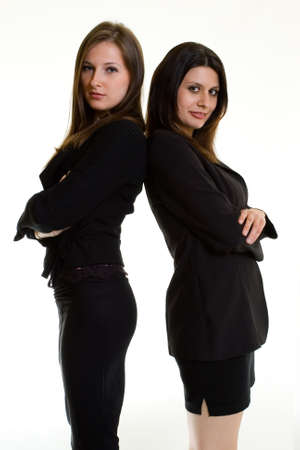 Two attractive confident young business women both wearing dark colored business suits standing back to back on white background Stock Photo - 925096