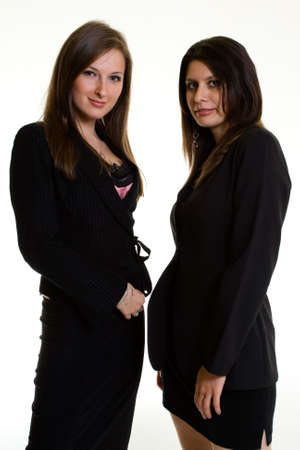 Two attractive confident business women both wearing dark colored business suits standing on white background Stock Photo - 925097