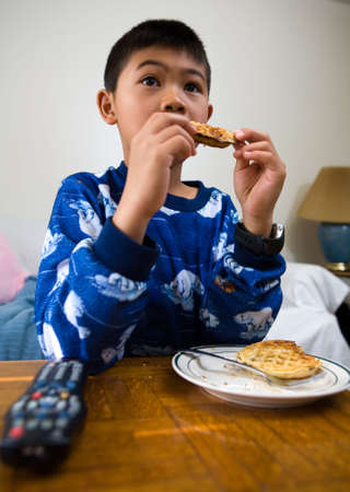 Young asian boy eating waffles for breakfast while looking engrossed in the television