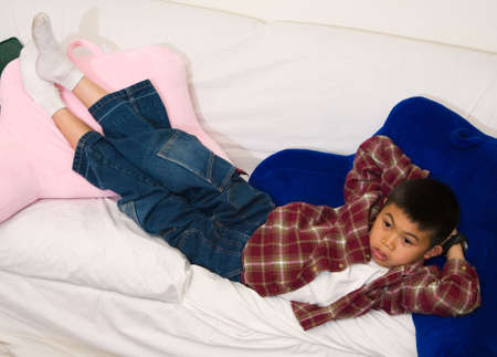 engrossed: Young asian boy laying down on a sofa while looking engrossed in the television Stock Photo