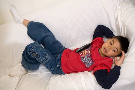Young asian boy comfortably laying down on the sofa holding the television remote control photo