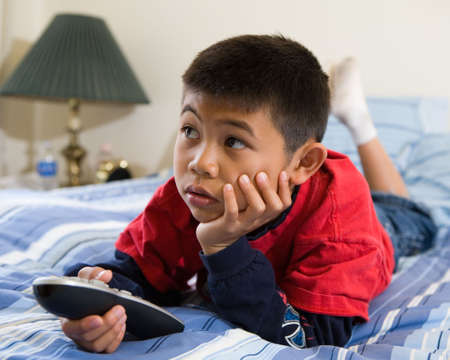 Young asian boy laying down on his stomach on the bed while looking engrossed in the television holding the remote control