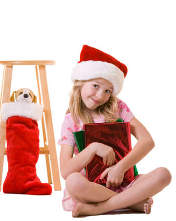 cute little eight year old girl sitting on floor with christmas presents holding a little stuffed dog Stock Photo - 944476