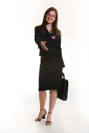 Attractive Business woman offering her hand for a handshake full body dressed in professional business suit and holding a briefcase standing on white background Stock Photo